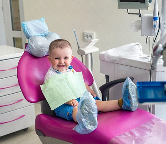 Young child smiling and sitting on dental chair