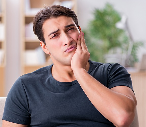 Man in need of emergency dentistry holding his cheek