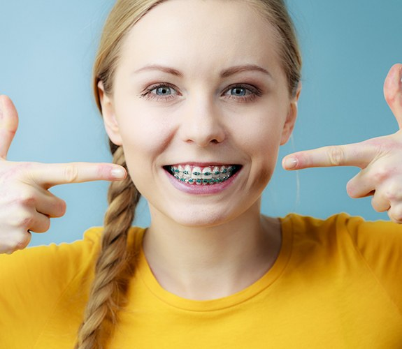 Woman with braces pointing to her smile