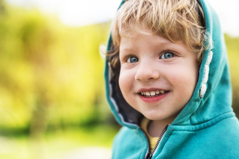 One-year-old boy with emerging teeth outside and smiling